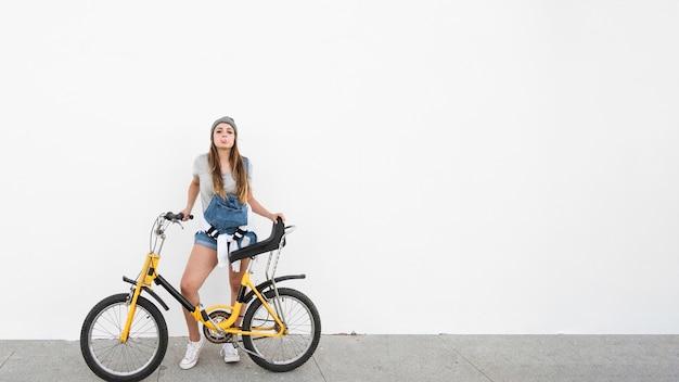 Mulher, com, bicicleta, soprando, pastilha elástica, ligado, calçada