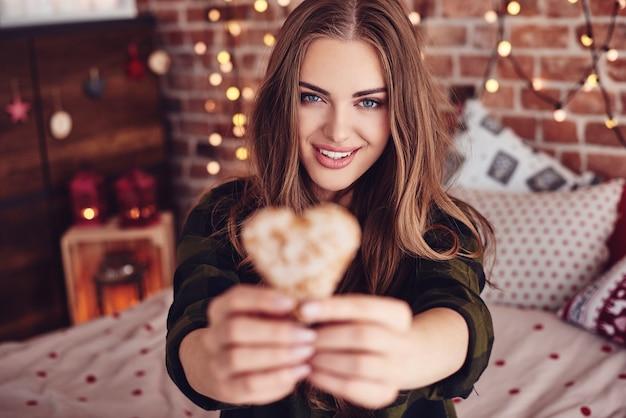 Mulher com biscoito do dia dos namorados posando