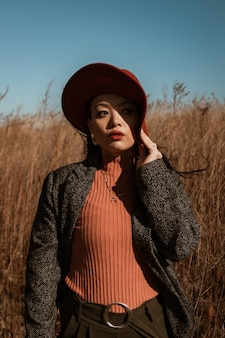 Mulher com blazer de manga comprida de bolinhas preto e branco e chapéu vermelho em um campo