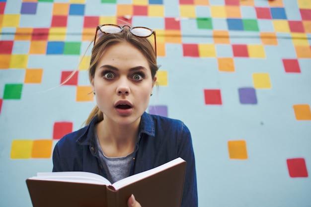 Mulher com bloco de notas nas mãos ao ar livre estilo de vida em casa parede multicolorida