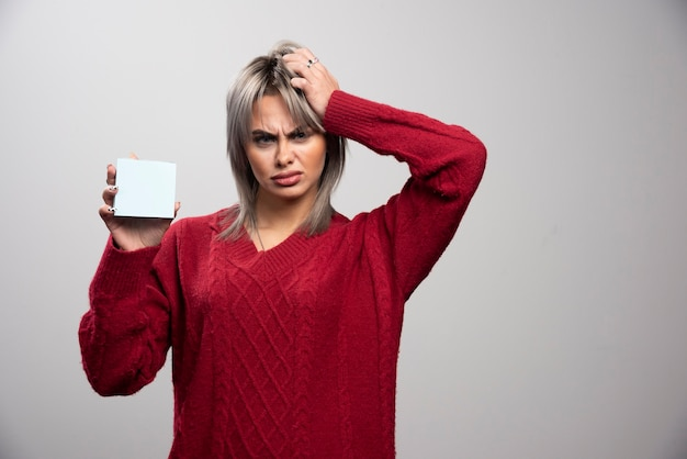 Mulher com bloco de notas parecendo zangada em fundo cinza.