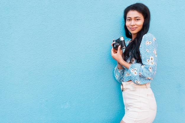 Mulher com blusa floral, segurando uma câmera