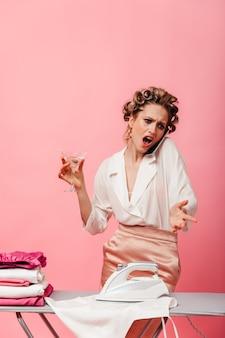 Mulher com bobes de cabelo falando indignada ao telefone e segurando uma taça de martini