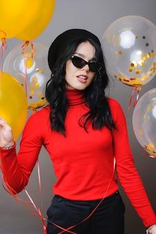Mulher com boina elegante e óculos de sol segurando um monte de balões