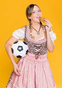 Mulher com bola comendo um pretzel