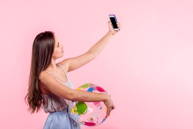 Mulher, com, bola praia, levando, selfie