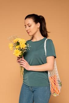 Mulher com bolsa de tartaruga e buquê de flores