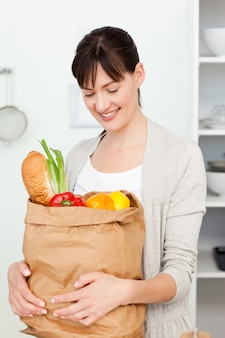 Mulher com bolsas de compras na cozinha