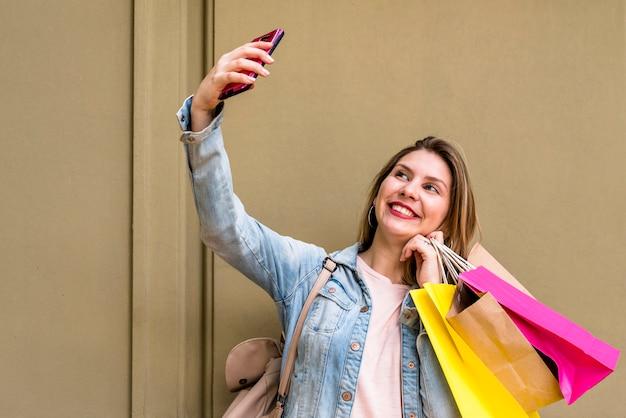 Mulher, com, bolsas para compras, levando, selfie, em, parede