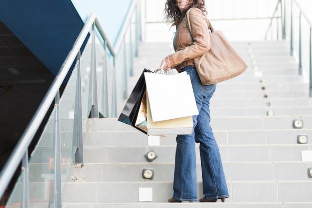 Mulher, com, bolsas para compras, ligado, escadas