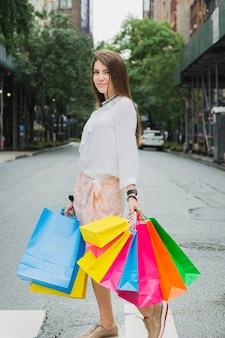 Mulher, com, bolsas para compras, ligado, estrada