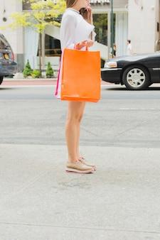 Mulher, com, bolsas para compras, perto, estrada