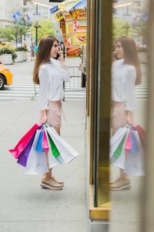 Mulher, com, bolsas para compras, telefonando