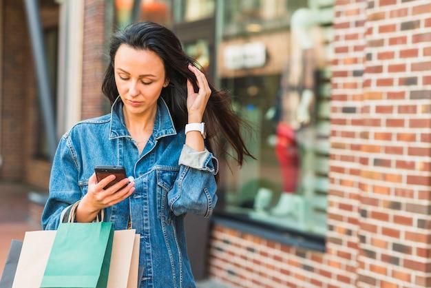 Mulher, com, bolsas para compras, usando, smartphone, em, centro comercial