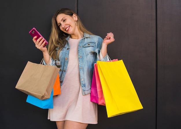 Mulher, com, bolsas para compras, usando, smartphone