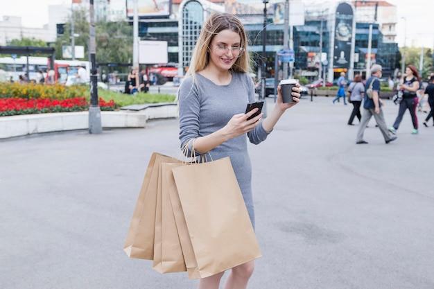 Mulher, com, bolsas para compras, usando, telefone móvel