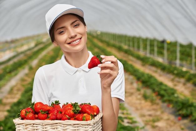 Mulher com boné branco segurando uma cesta com morangos maduros