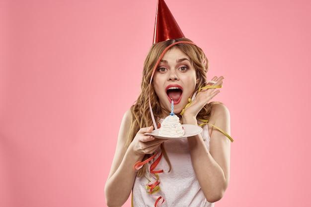 Mulher com boné vermelho, bolo de festa de aniversário rosa
