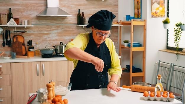 Mulher com bonete peneirando a farinha na mesa de madeira pronta para cozinhar. padeiro sênior aposentado com avental, uniforme de cozinha, borrifando, peneirando e espalhando ingredientes refogados, assando pão caseiro.