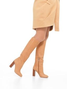 Mulher com botas de outono bege isolada no branco
