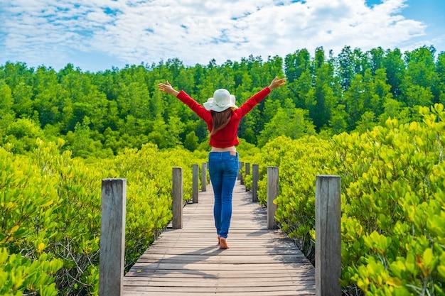 Mulher, com, braços levantaram, em, ponte madeira, em, tung prong, tanga