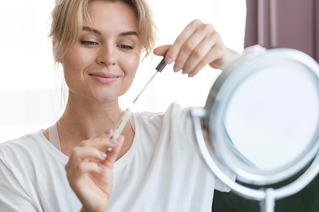 Mulher com brilho labial e espelho