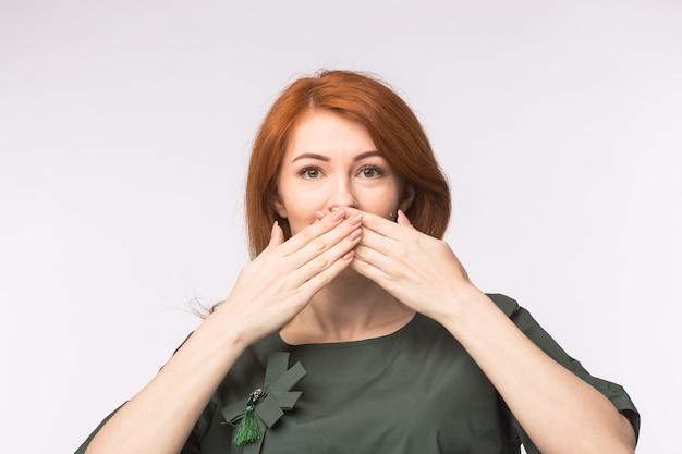 Mulher com cabeça de ré com as palmas das mãos sobre a boca em fundo branco