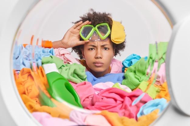 Mulher com cabelo afro usa máscara de mergulho em poses através da porta da máquina de lavar, cercada por roupas multicoloridas e o detergente lava a roupa em casa