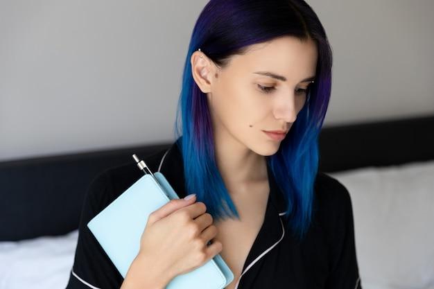Mulher com cabelo azul no quarto segurando um bloco de notas