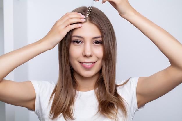 Mulher com cabelo bonito aplica vitaminas para o crescimento do cabelo