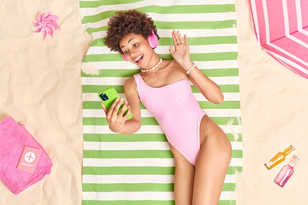 Mulher com cabelo cacheado acena palma em gesto de olá segura celular verde faz videochamada na praia usa biquíni rosa ouve música com fones de ouvido desfruta de bom descanso