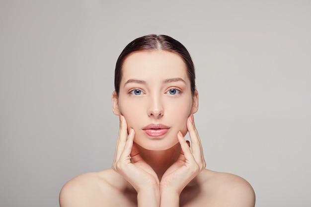 Mulher com cabelo castanho limpa pele fresca ombros nus segurando a mão no rosto posando