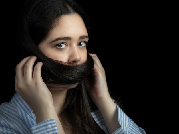Mulher com cabelo cobrindo a boca dela. retrato.