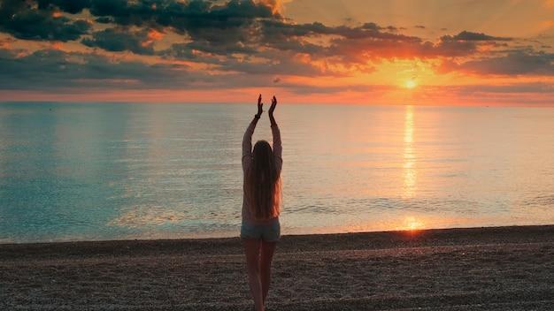 Mulher com cabelo comprido caminhando para o mar e levantando as mãos, olhando para a vista traseira do pôr do sol