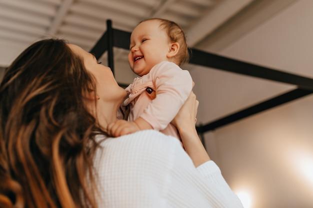Mulher com cabelo comprido faz cócegas e vomita bebê rindo num suéter de cor clara.