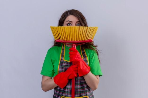 Mulher com cabelo comprido ondulado usando avental e luvas de borracha se escondendo atrás do esfregão em pé