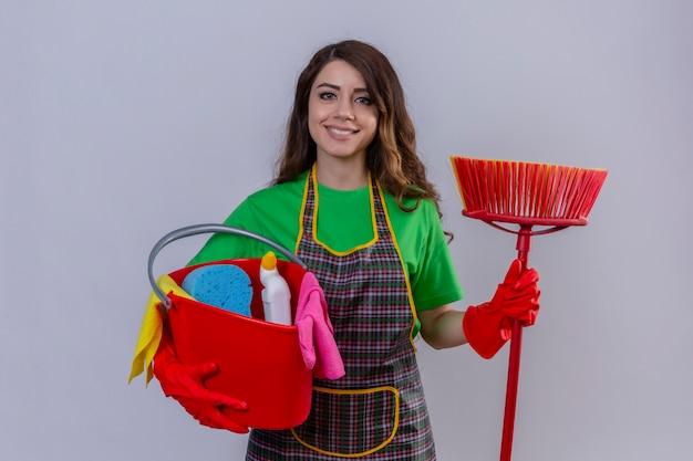 Mulher com cabelo comprido ondulado usando avental e luvas de borracha segurando balde com ferramentas de limpeza e esfregona com rosto feliz sorrindo alegre em pé