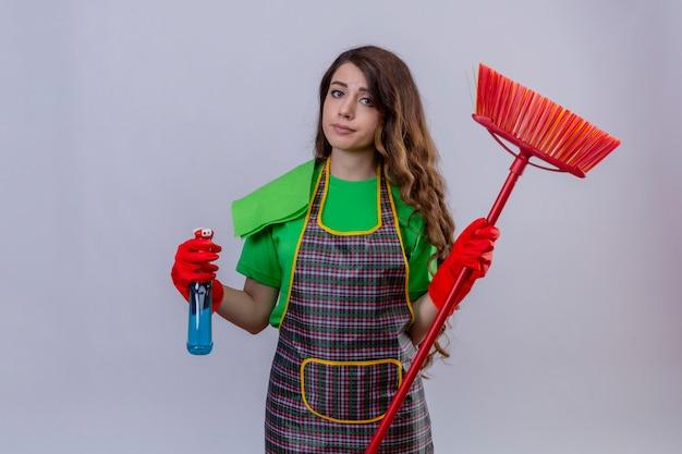 Mulher com cabelo comprido ondulado usando avental e luvas de borracha segurando spray de limpeza e esfregão parecendo cansada com expressão cética em pé