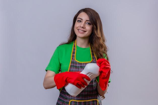 Mulher com cabelo comprido ondulado usando avental e luvas de borracha segurando um frasco de material de limpeza, parecendo positiva e feliz em pé e sorrindo