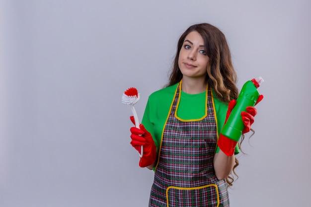 Mulher com cabelo comprido ondulado usando avental e luvas de borracha segurando uma escova e uma garrafa com material de limpeza com sorriso cético em pé