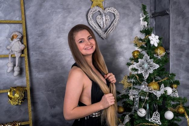 Mulher com cabelo comprido posando com pinheiro