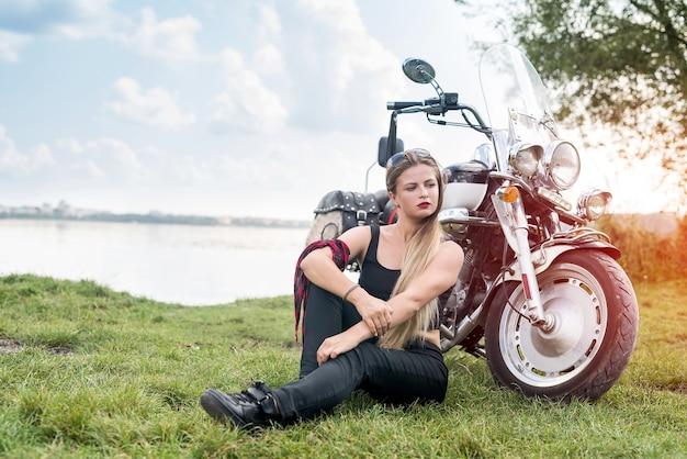 Mulher com cabelo comprido posando perto de uma motocicleta