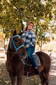 Mulher com cabelo curto, andando a cavalo no parque de outono