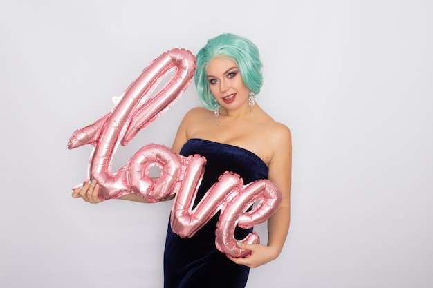 Mulher com cabelo curto de menta no vestido de veludo azul escuro, segurando o balão com a palavra amor