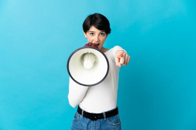 Mulher com cabelo curto em um espaço isolado gritando em um megafone para anunciar algo enquanto aponta para a frente