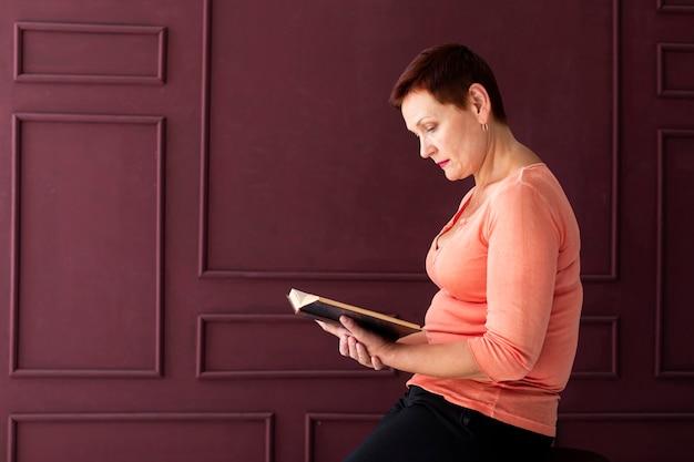 Mulher com cabelo curto, lendo uma revista