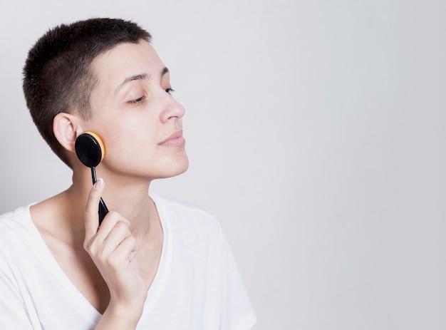 Mulher com cabelo curto, limpando o rosto com uma escova