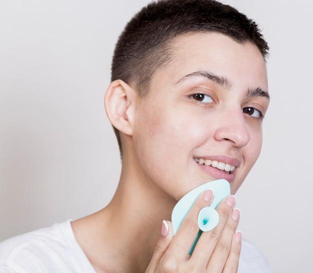 Mulher com cabelo curto, limpando o rosto enquanto olha para a câmera