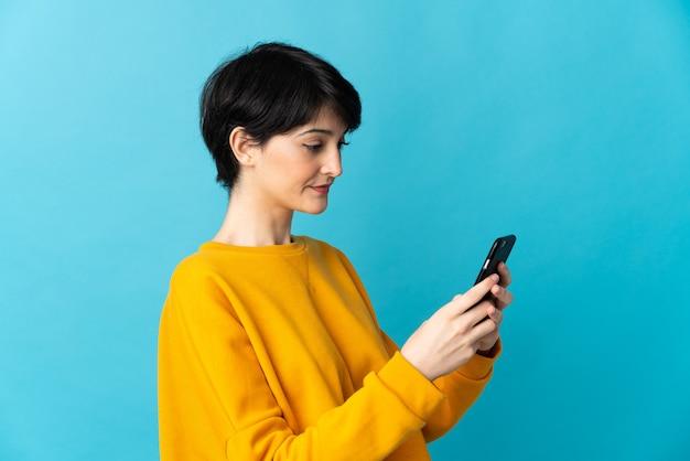 Mulher com cabelo curto muito isolado enviando mensagem ou e-mail pelo celular