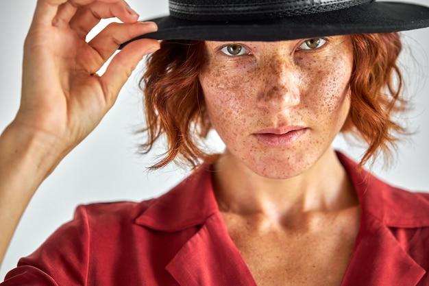 Mulher com cabelo curto ruivo natural e elegante chapéu preto olhando para a câmera